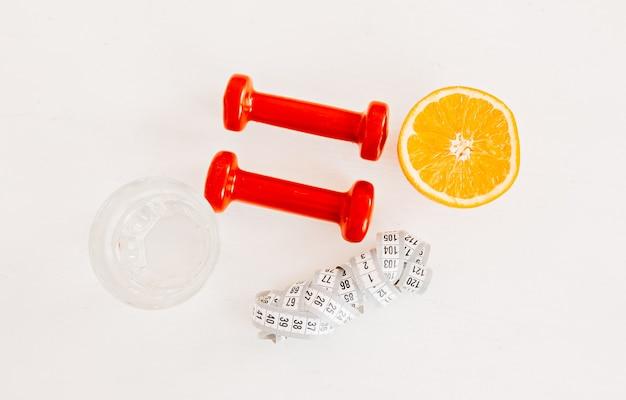Un centimetro, un'arancia, un bicchiere d'acqua e manubri rossi. assistenza sanitaria, dieta e concetto di sport