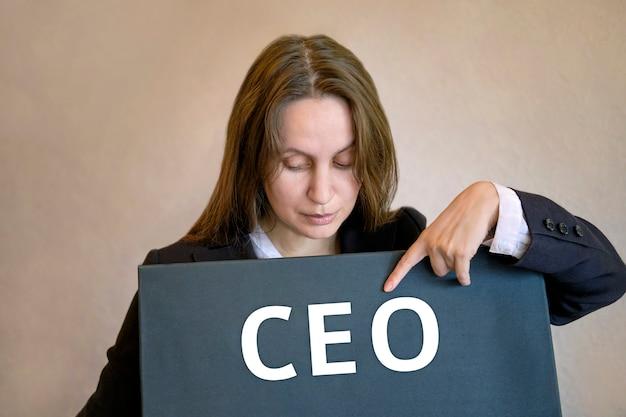 Concetto di affari finanziari ceo. la ragazza donna si alza e punta il dito contro l'iscrizione sul bordo nero