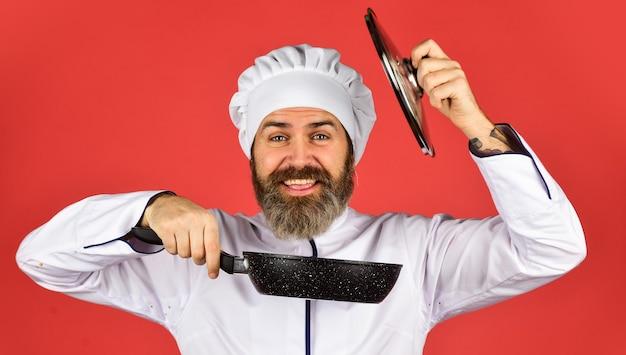 Padella applicata in ceramica. preparazione del cibo in cucina. cucinare il concetto di cibo. padella di alta qualità. uniforme bianca del cuoco dell'uomo barbuto. cucinare come un professionista. pasto facile e gustoso preparato in casa. colazione fatta in casa.