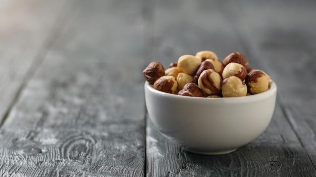 Ciotola in ceramica con nocciole tostate sul tavolo rustico. preparato con la raccolta delle nocciole.