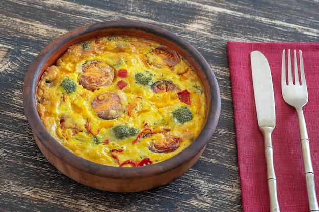 Ciotola in ceramica con frittata di verdure, cibo vegetariano semplice. frittata con uova, pomodoro, peperone, cipolla, broccoli e formaggio su tavola di legno, primo piano. frittata di uova all'italiana