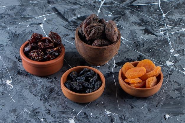 Ciotole in ceramica di gustosa frutta secca su superficie di marmo.