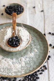 Ciotole in ceramica con farina di fagioli neri e fagioli secchi con un cucchiaio di legno in primo piano. mangiare sano e concetto vegetariano. ingrediente tradizionale cugino latinoamericano