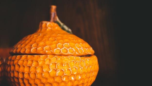 Un contenitore in ceramica a forma di mandarino con coperchio ricoperto di glassa si trova su un ripiano in legno. sfondo scuro e posto per il testo,