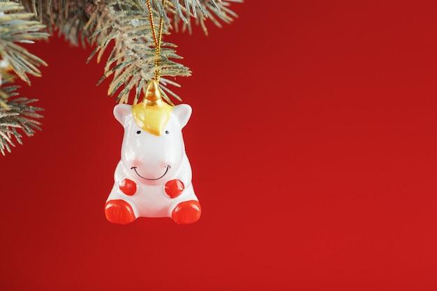 Figura in ceramica di un unicorno su un ramo di abete rosso