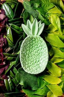 Piatto di ananas verde in ceramica su fondo composto da diverse foglie verdi e rosse, sfumatura verde. copia spazio. layout creativo della natura, vista dall'alto, piatto. concetto di cibo ecologico