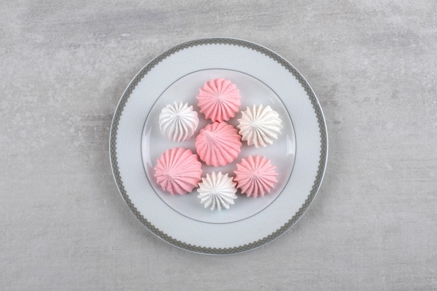 Piatto in ceramica di dolci meringa bianchi e rosa sulla superficie della pietra.