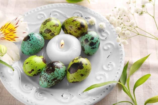 Piatto in ceramica con uova di pasqua e candela su sfondo chiaro
