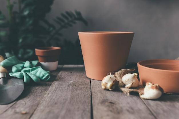 Vasi in ceramica sul vecchio tavolo in legno grigio, bulbi di tulipani, guanti verdi, pala da giardino. foto di alta qualità