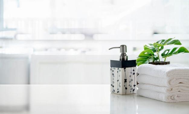 Shampoo in ceramica, bottiglia di sapone e asciugamani sul bancone sopra la stanza della cucina. tavolo bianco e copia spazio.