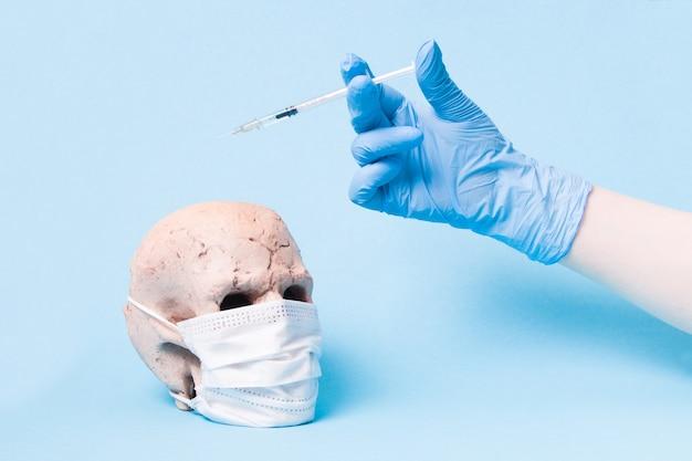 Teschio in ceramica in una maschera medica protettiva bianca e una mano in un guanto di gomma blu tiene una siringa da insulina con la medicina su uno sfondo blu