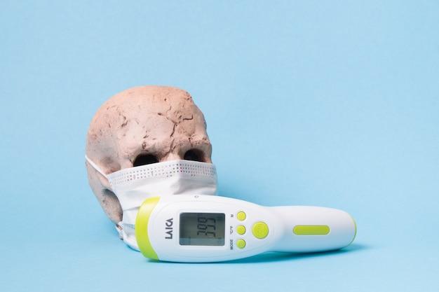 Teschio in ceramica con maschera medica protettiva bianca e termometro a infrarossi senza contatto su superficie blu