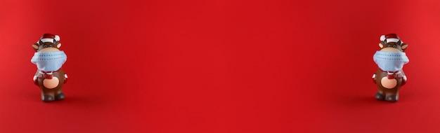 Statuette in ceramica di bue in mascherina medica su fondo rosso. ampio banner con copia spazio. simbolo del nuovo anno 2021.