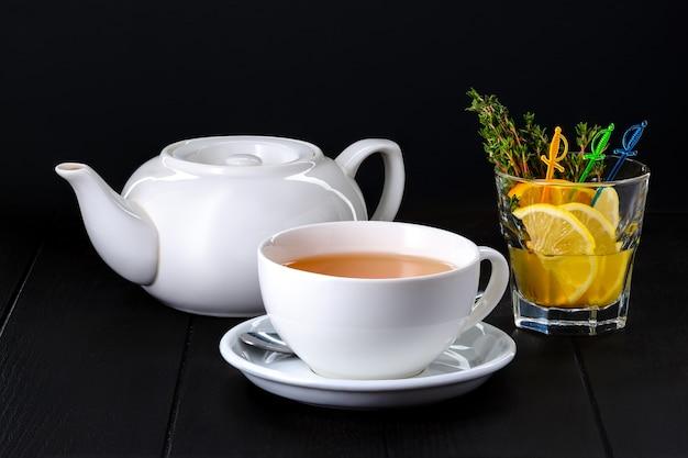 Teiera in ceramica e tazza con tè echinocea su sfondo scuro