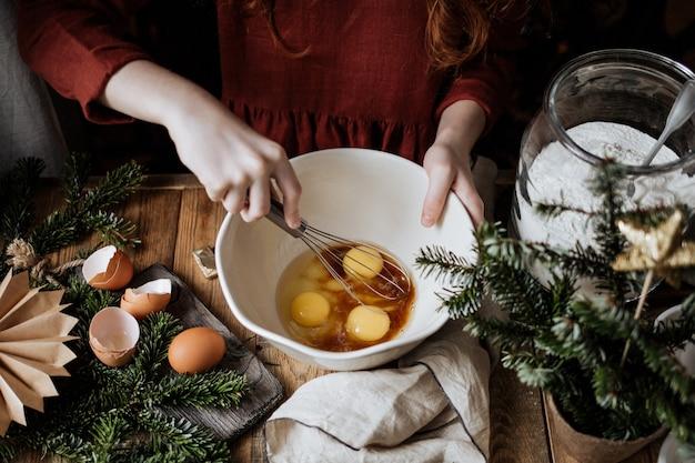 In una ciotola bianca di ceramica sbatti insieme lo zucchero di canna e le uova.
