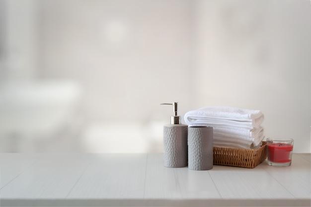 Shampoo o sapone di ceramica, asciugamani sul bancone di marmo superiore con lo spazio della copia sul fondo del bagno.
