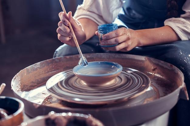 La ragazza ceramista dimostra il processo di realizzazione di piatti in ceramica utilizzando la vecchia tecnologia