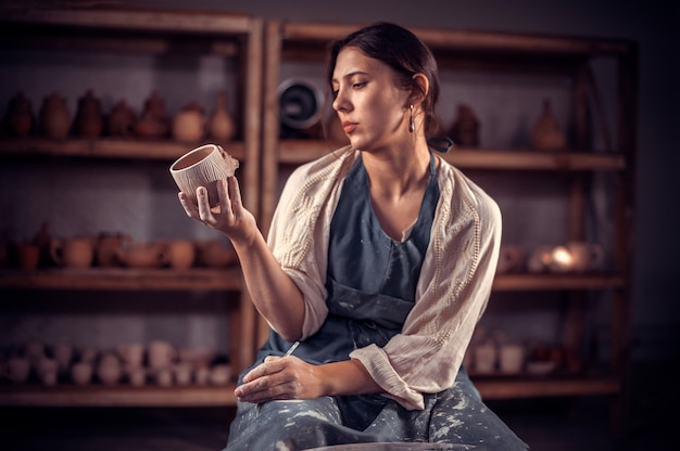 Una donna ceramista mostra il prodotto finito in argilla nel laboratorio di ceramica. laboratorio di ceramica.