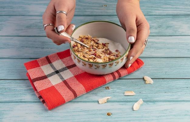 Ciotola di cereali con frutta secca su un tavolo di legno blu