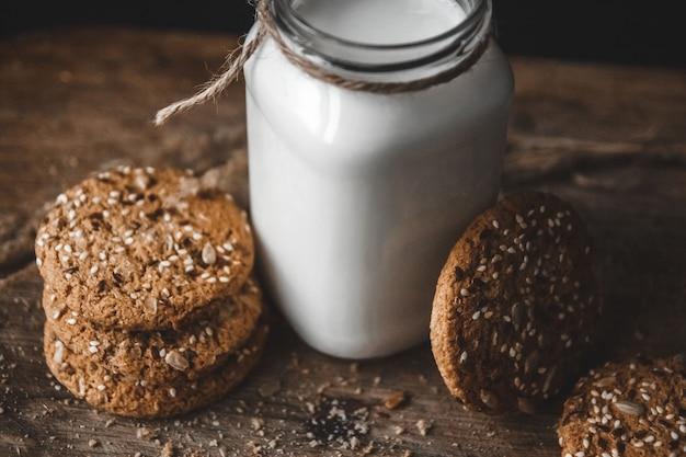 Biscotti ai cereali con una brocca di latte su uno sfondo di legno.