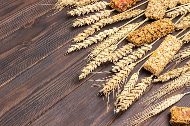 Barrette di cereali energia muesli e spighette di grano su una superficie di legno scuro. colazione equilibrata di proteine. vista dall'alto. copia spazio