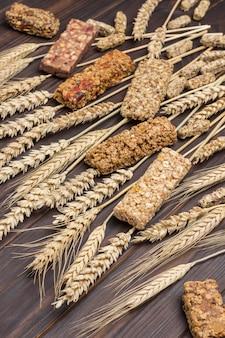 Barrette di cereali energia muesli e spighette di grano su una superficie di legno scuro. fonte naturale di energia. vista dall'alto. avvicinamento