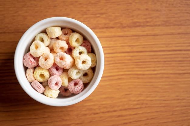 Fiocchi di cereali in una ciotola in ceramica con spazio di copia, concetto di colazione.cibo con delizioso gusto fruttato e colori fruttati.è fatto con mais, grano e orzo.