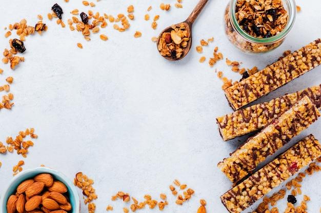 Barretta di cereali muesli con noci, frutta e bacche su un tavolo di pietra bianca. barretta di muesli. snack salutare. vista dall'alto.