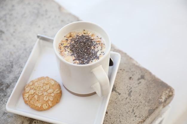Cereali sul latte in tazza con colazione a mano di donna