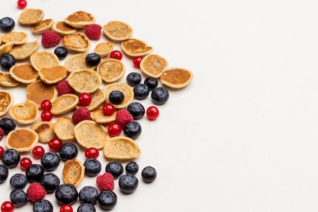 Frittelle di cereali e frutti di bosco su sfondo bianco. lay piatto. copia spazio