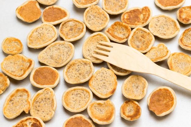 Frittelle di cereali su superficie bianca e forcella di legno. lay piatto.