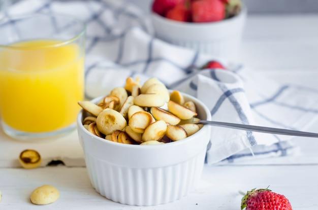 Frittella di cereali con fragole e un bicchiere di succo d'arancia