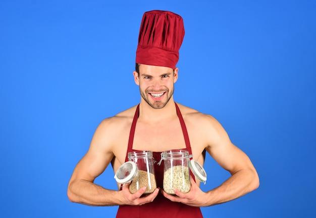 Cereali, semola, alimenti biologici, dieta, cibo sano. lo chef con cappello bordeaux e grembiule tiene in mano barattoli con cereali. concetto di dieta sana. il cuoco professionista maschio tiene un barattolo di vetro con cereali.
