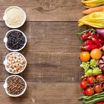 Cereali e legumi in ciotole e verdure su una tavola di legno con la vista superiore dello spazio della copia