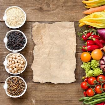 Cereali e legumi in ciotole e verdure su una tavola di legno con la vista superiore dello spazio della copia su carta