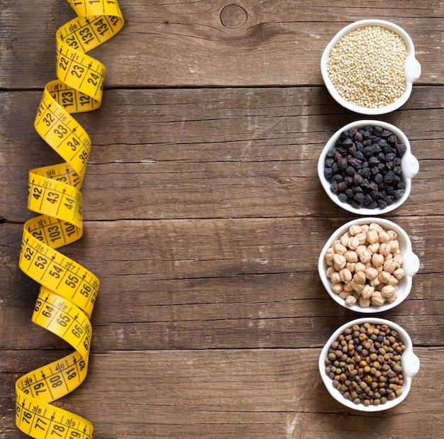 Cereali e legumi in ciotole con tipo di misurazione su una vista di legno del piano d'appoggio con lo spazio della copia
