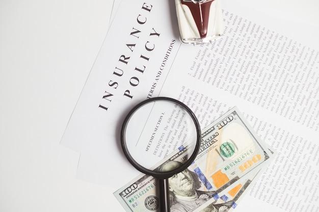 Certificato di assicurazione auto e polizza con auto e banconote da un dollaro