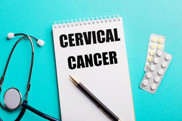 Cancro cervicale scritto in un blocco note bianco vicino a uno stetoscopio