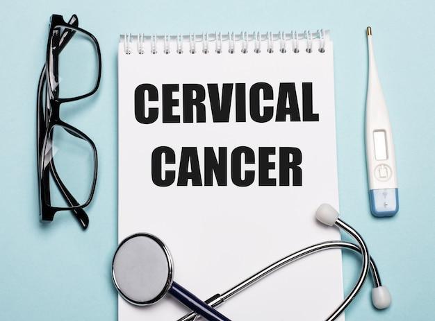 Cancro cervicale scritto su un blocco note bianco accanto a uno stetoscopio, occhiali protettivi e un termometro elettronico su sfondo azzurro.