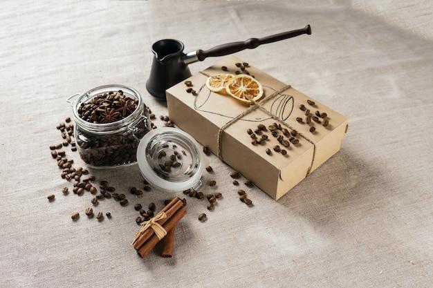 Cezve e chicchi di caffè tostati in scatola su un tavolo rustico, cannella e limone essiccato.
