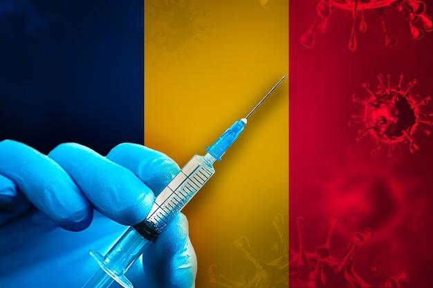 Campagna di vaccinazione del ciad covid19 la mano in un guanto di gomma blu tiene la siringa davanti alla bandiera