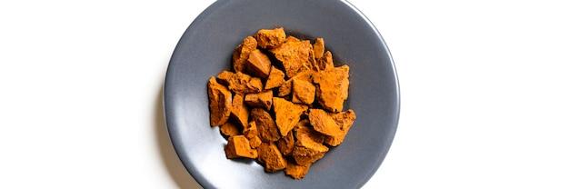 Fungo chaga. piccoli pezzi secchi tritati di betulla albero fungo chaga in un piatto rotondo isolato su uno sfondo bianco. concetto di medicina naturale alternativa. banner
