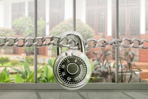Catena in acciaio metallico con lucchetto e vetro della finestra e sfondo con vista sul giardino