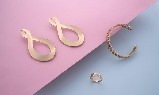Bracciale e anello a forma di catena con coppia di orecchini moderni dorati su sfondo rosa e blu