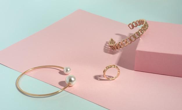 Forma di catena e oro con braccialetti di perle e anello su carta rosa e verde