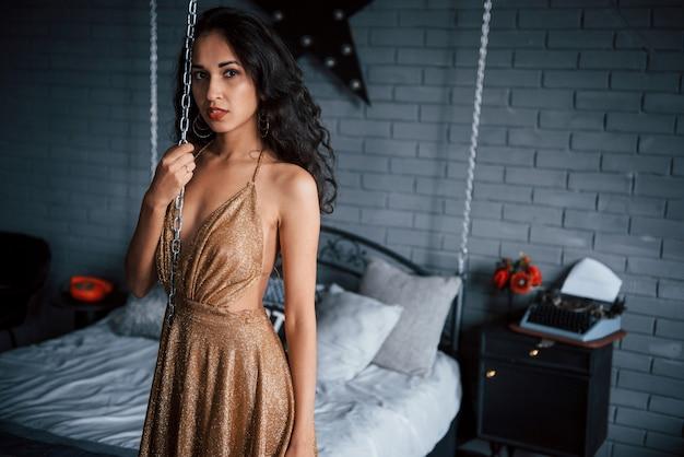 Letto incatenato. ragazza in abito dorato si trova nella parte anteriore del letto bianco in appartamenti di lusso
