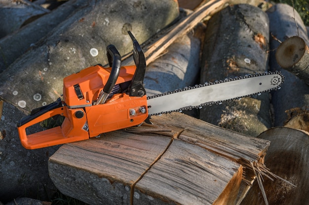 Motosega che si trova su un mucchio di legna da ardere nel cortile su uno sfondo di legna da ardere e alberi tagliati da una motosega.