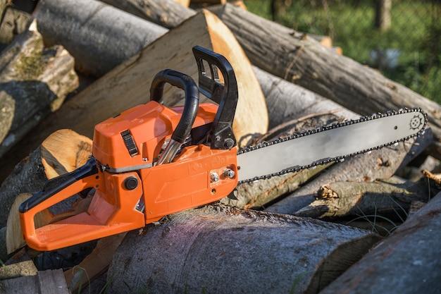 Motosega che si trova su un mucchio di legna da ardere nel cortile, legna da ardere e alberi tagliati da una motosega.