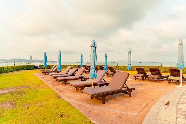 Piscina con sedia o piscina per lettino e ombrellone intorno alla piscina con sfondo di spiaggia del mare a pattaya in thailandia
