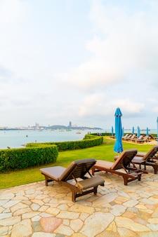 Sedia piscina o piscina letto e ombrellone intorno alla piscina con spiaggia del mare a pattaya in thailandia